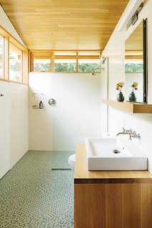 In the bathroom, a thin pane of glass separates the shower; an Aquaplane sink by Lacava hovers above   a built-in vanity illuminated by a lean Adelphi light by Oxygen Lighting; and blue-green glass penny tiles by Terra Verre decorate the floor. The absence of a door, combined with windows on two sides, makes the bathroom feel like a continuation of the overall space.