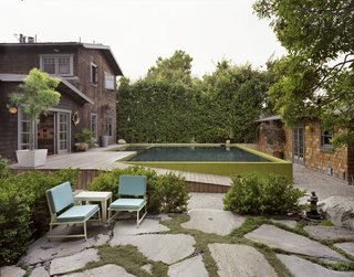 Across the path is the resident's favorite spot from which to take in the aquatic tableau: a rock garden and sitting area created by landscape designer Tory Polone. Chairs rest near the a hidden grade-level gas fire pit—an on-demand campfire.