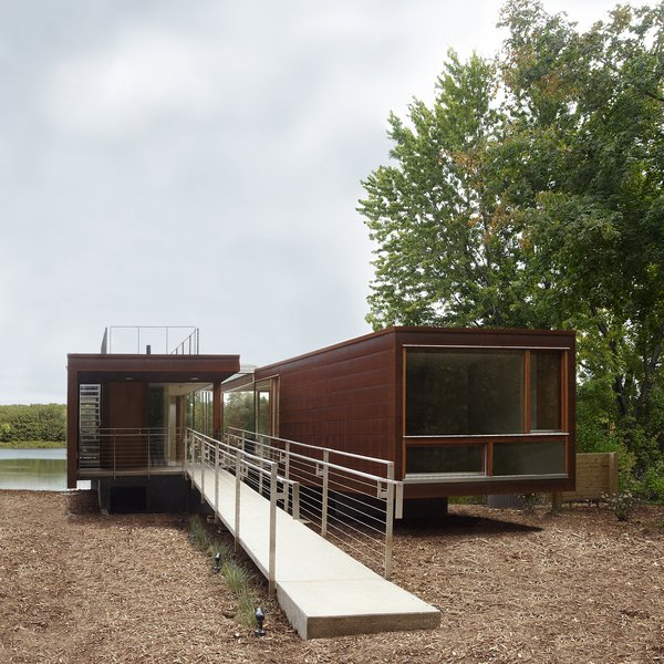 """Architect Jim Garrison of Brooklyn-based Garrison Architects was asked to design a lakeside retreat for visiting families at a boarding school for troubled teens, Star Commonwealth, in Albion, Michigan. To drastically reduce academic interruption and cut site noise, Garrison decided early on to create an 1,100-square-foot modular building dubbed Koby, with two bedrooms on opposite sides of the structure and a common dining area in the middle """"as a therapeutic space for families to gather and eat together."""""""