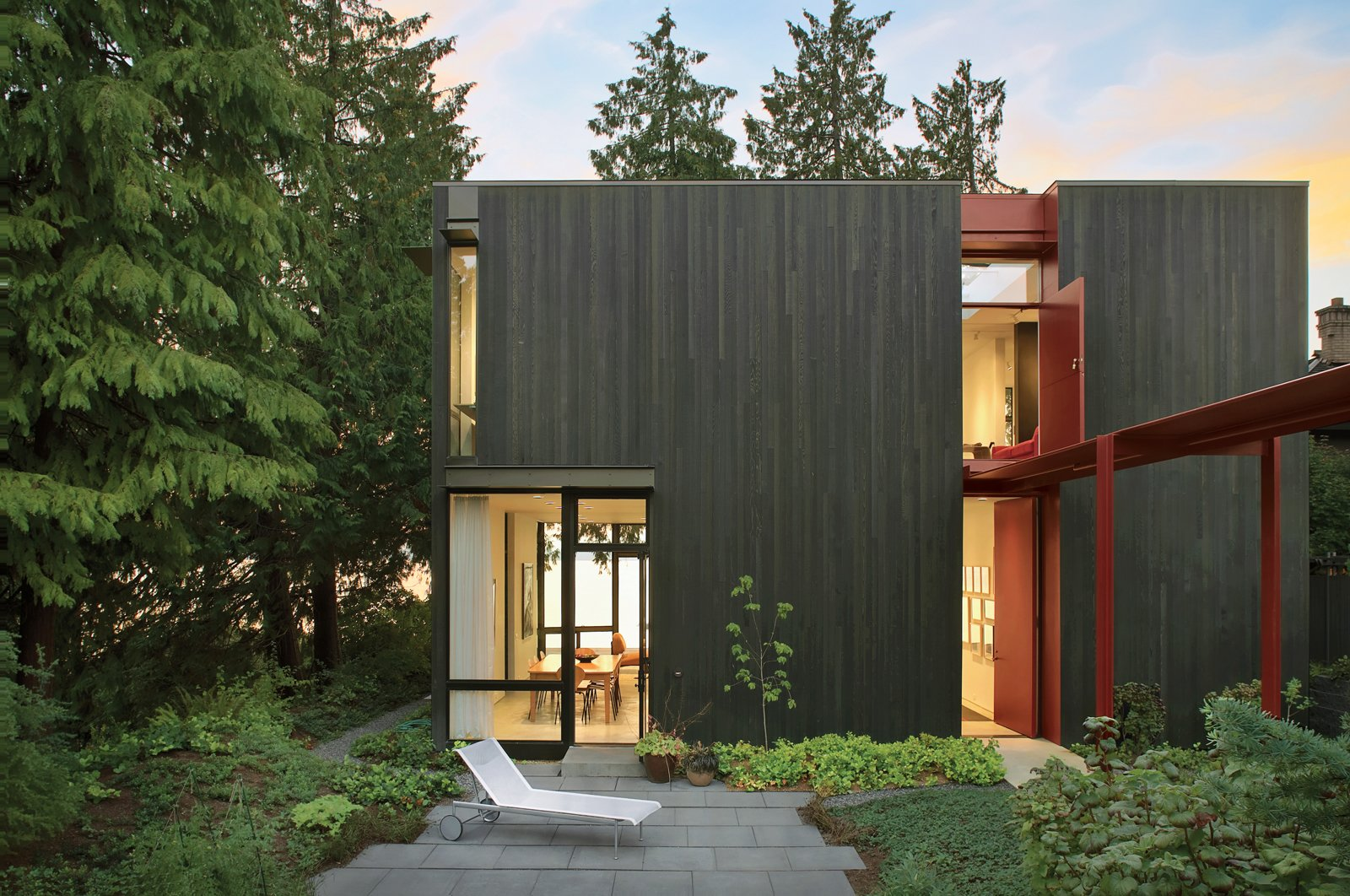 """A second-story Dutch door above the canopy ushers in sunlight and breezes. """"Light is really important in the Pacific Northwest because it's dark for most of the year,"""" says the resident. The cedar-clad facade is pierced with thoughtfully placed windows, which frame views and """"actively engage the idiosyncratic nature of the place,"""" says architect Tom Kundig.  Hail Cedar: 7 Houses that Make Use of Cedar Wood by Diana Budds from Modern Steel Homes"""