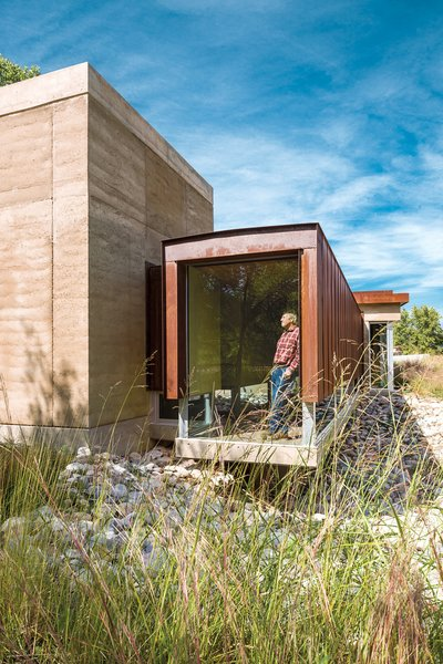 """Roger and Mary Downey's 3,200-square-foot rammed-earth home seems to float next to the forest along the Rio Grande in Corrales, New Mexico. While the home's design and materials nod to the neighboring adobe farmhouses and agricultural sheds, architect Efthimios Maniatis of Studio eM Design calls them an amalgam of """"modern contemporary regionalism,"""" governed by Roger's strict mandate for minimalism."""