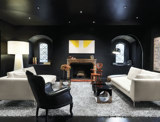 Turin embraced the dark in her striking living room—the deep paint is Le Corbusier's 4320J from Les Couleurs Suisse. An iconic Arco lamp by Achille and Pier Giacomo Castiglioni for Flos, Charles sofas by Antonio Citterio for B&B Italia, an Extra Big Shadow floor lamp by Marcel Wanders for Cappellini, and a painting over the mantel by Martin Barré shed a little light.