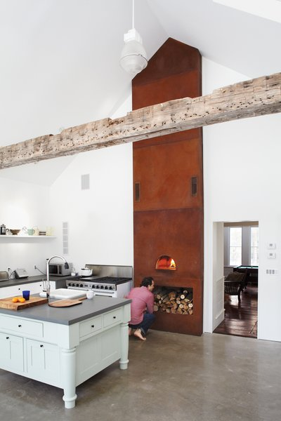 In the kitchen of Floating Farmhouse in Eldred, New York, a custom-built wood-fired oven extends up to the ceiling, accentuating its steep pitch. Photo by Mark Mahaney.