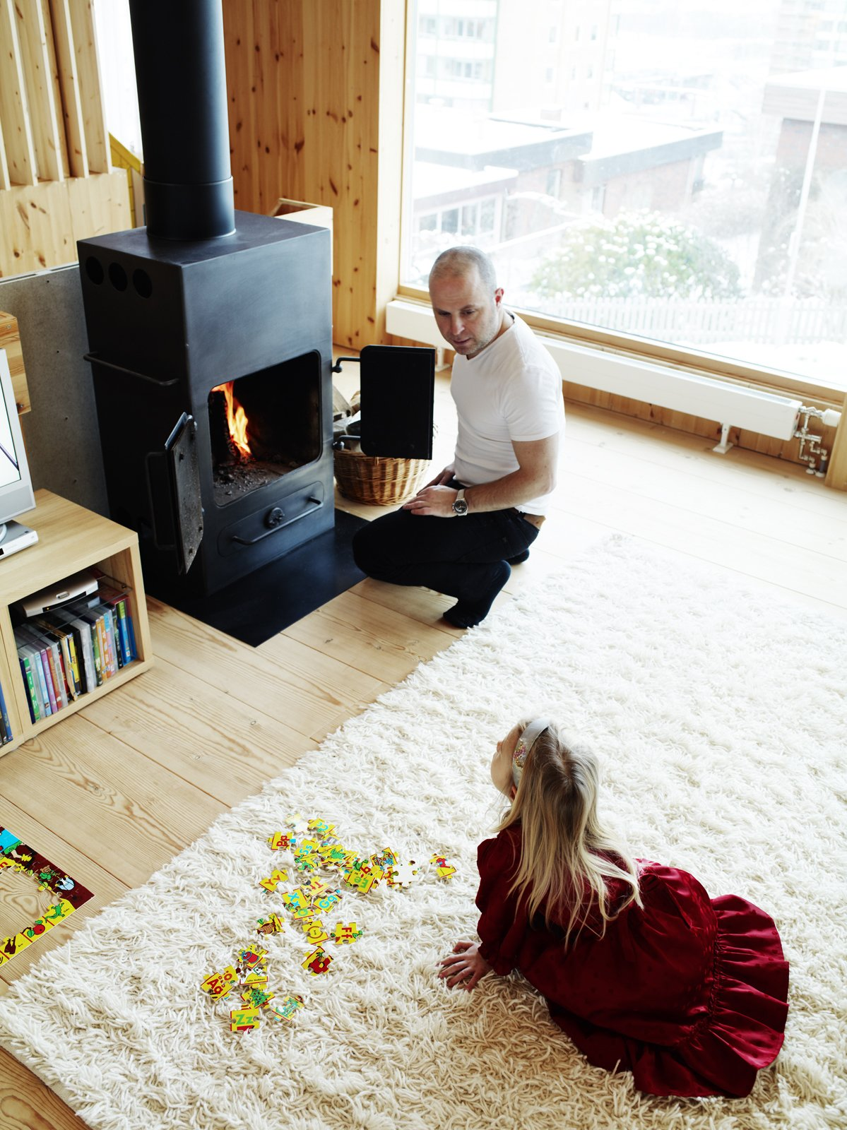 Living Room, Wood Burning Fireplace, Standard Layout Fireplace, Light Hardwood Floor, Rug Floor, and Storage Architect Per Bornstein and his daughter Velma relax in the living room. The woodburning stove was a second-hand store find. Photo by Pia Ulin.  97+ Modern Fireplace Ideas from Knotty by Nature