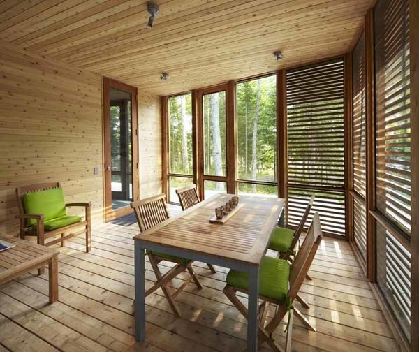Walls and ceilings fold like origami, sheltering the interior with tent-like flaps. On the enclosed porch, horizontal slats, a modern hallmark often seen in the pages of Dwell, is palatable for a traditionalist thanks to generous use of cedar. Photo by Shai Gil.