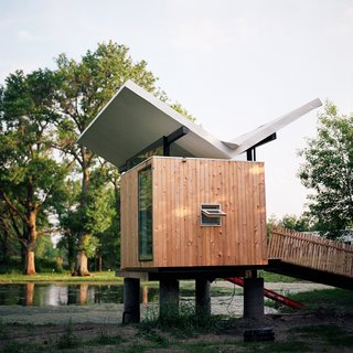 Perched above a pond on 14 acres in Champaign, Illinois, this hut was designed for enjoying tea and meditation. Dominating the 97-square-foot structure is a butterfly roof, which channels rainwater to a central spout to be directed to the pond. Adding to the zen experience are water reflections that are projected onto the soffit throughout the day.