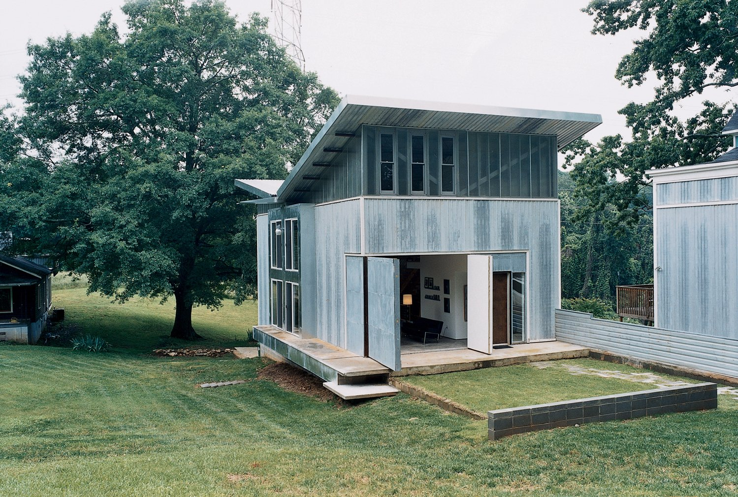 Exterior, Mid-Century, Cabin, House, Butterfly, and Metal The decidedly nontraditional structure includes a front wall that opens the living room onto the front yard—and to the rest of the neighborhood, which has enthusiastically welcomed the house and its owner.  Best Exterior Butterfly Cabin Photos from Mid-City Modern