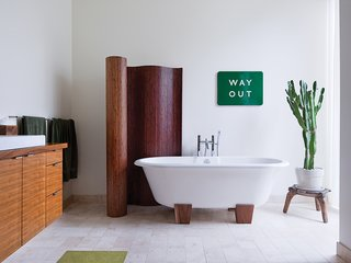The master bathroom has a bamboo screen and a Deauville tub by Victoria + Albert. A vintage enameled metal sign from the London Underground is framed by the screen and a cactus that sits atop an African stool. Read more about  the eclectic South Minneapolis residence here.