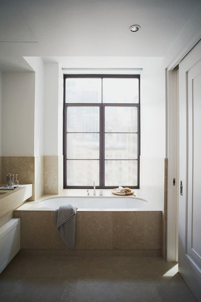Each bathroom in Huys is decked out in Chambolle stone slab, from flooring to countertop to wall tiles. Piet Boon-designed lighting illuminates a Duravit sink, Dornbracht fixtures in matte platinum, and a Kaldewei soaking tub. The floors are equipped with radiant heating by NuHeat.  Photo 5 of 6 in 5 Great Rooms from New Dutch Apartment Huys in New York City