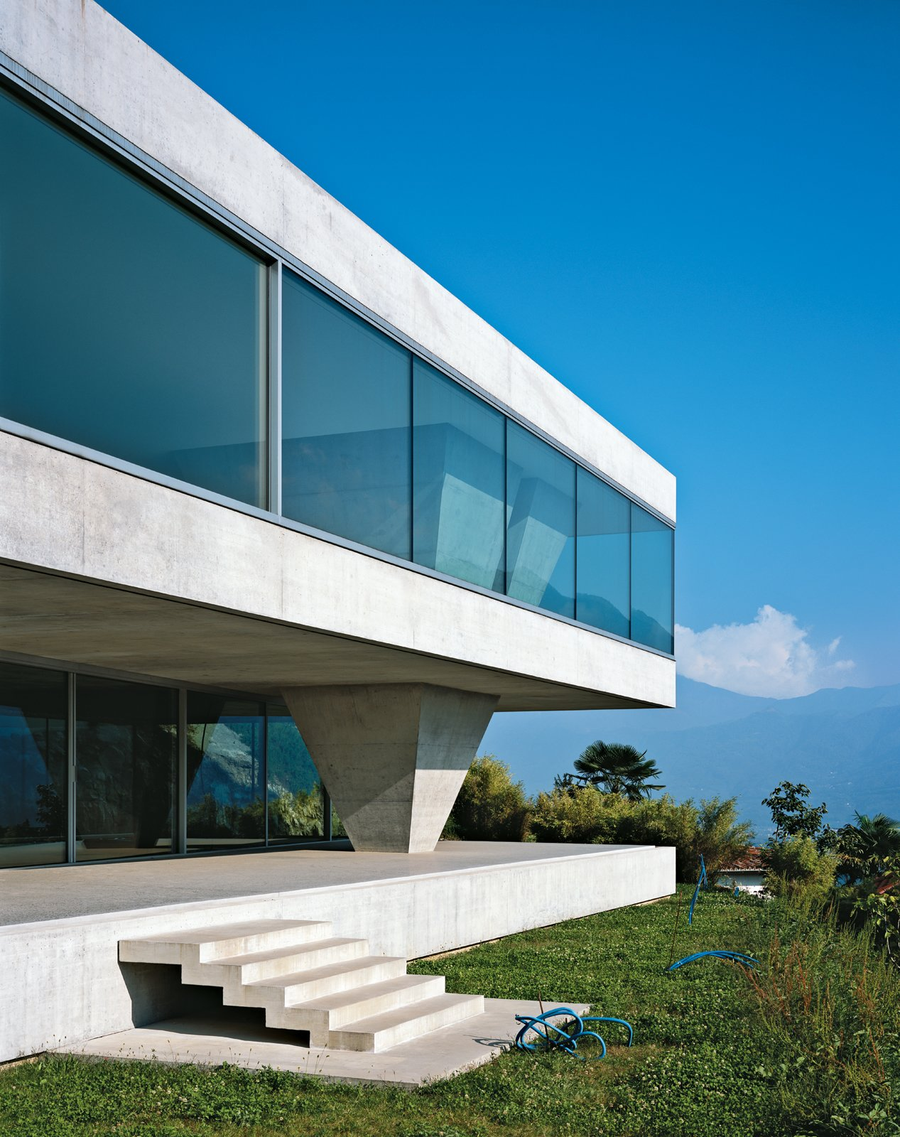 Exterior, Concrete Siding Material, Flat RoofLine, House Building Type, and Glass Siding Material Casa ai Pozzi makes a bold statement on the mountainous shores of Lake Maggiore. The windows that wrap around this concrete villa afford stunning views of the Swiss Alps, and the inverted pyramid that supports the structure subtly mirrors the surrounding mountain peaks.  Photo by: Hélène Binet  Concrete from A Concrete Double Villa in Switzerland