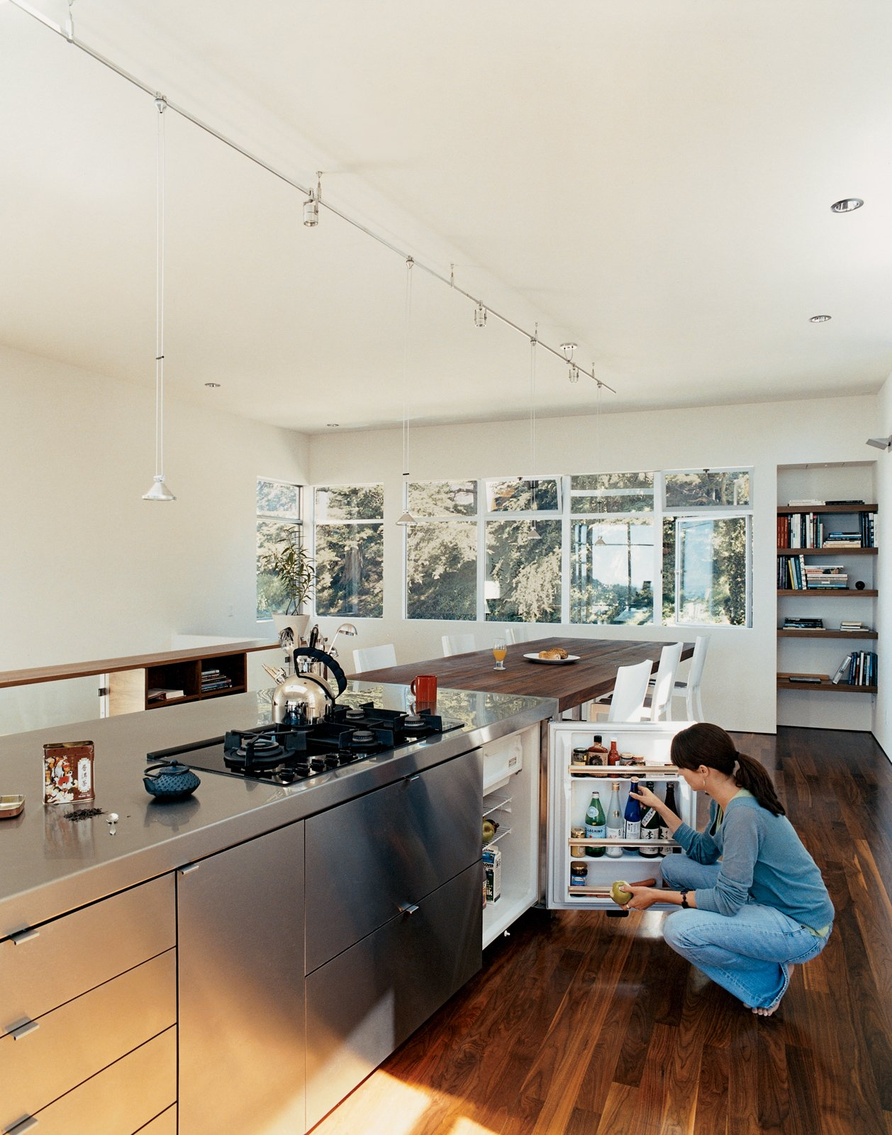 "Kitchen, Medium Hardwood Floor, Metal Counter, Cooktops, and Refrigerator Neither the owner, a self-declared ""card-carrying-modernist,"" or his girlfriend, Stephanie Kiriakopolos, miss having a big bulky refrigerator.  Tiny Kitchens We Love by Erika Heet from Standout in a Crowd"