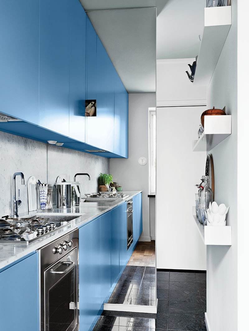 Kitchen, Marble Counter, Range, Stone Slab Backsplashe, Colorful Cabinet, Cooktops, and Undermount Sink A mirror measuring 8.5 by 3.3 feet makes the renovated kitchen feel more expansive. Photo by: Jonas Ingerstedt  Tiny Kitchens We Love by Erika Heet from Modern Tiny Kitchen Remodel in Sweden