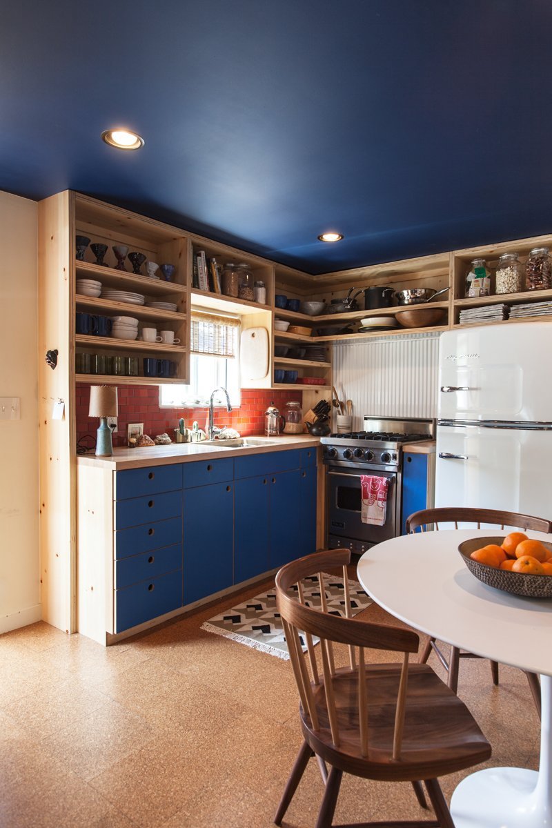 "Kitchen, Colorful, Open, Recessed, Refrigerator, Wall Oven, Range, Ceramic Tile, Metal, and Wood The kitchen cabinetry echoes the new blue ceiling. The brick tile is from Heath Ceramics, as is the dinnerware. Behind the Viking stove is powder-coated corrugated metal (""Very trailer,"" says the designer). The refrigerator is from Big Chill. On the table is a bowl by Victoria Morris.  Best Kitchen Metal Range Photos from A Modern Beachside Trailer Home in Malibu"