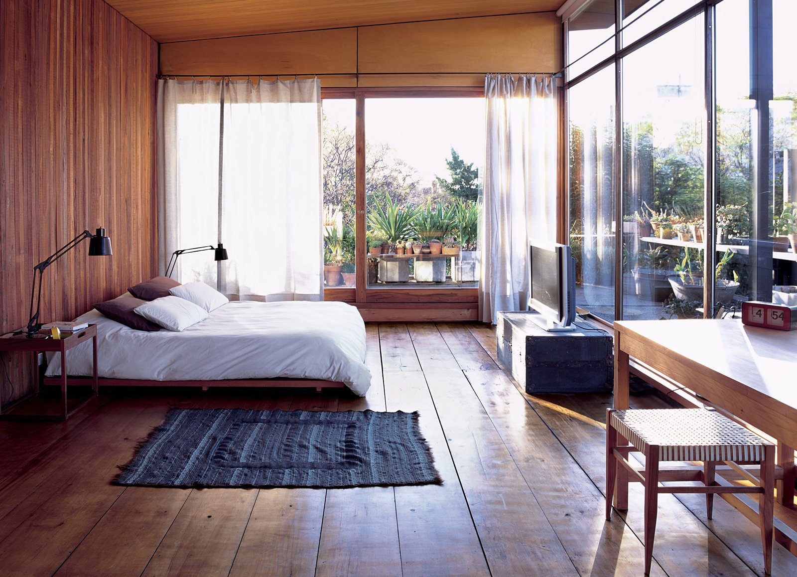 Bedroom, Bed, Medium Hardwood Floor, and Table Lighting A COZY AND MODERN INDOOR-OUTDOOR BEDROOM IN BUENOS AIRES  In Argentinean architect and furniture designer Alejandro Sticotti's bedroom, dappled sunlight and reclaimed-wood floors and walls give the room a warm, peaceful feel.  Bedroom from Net Assets