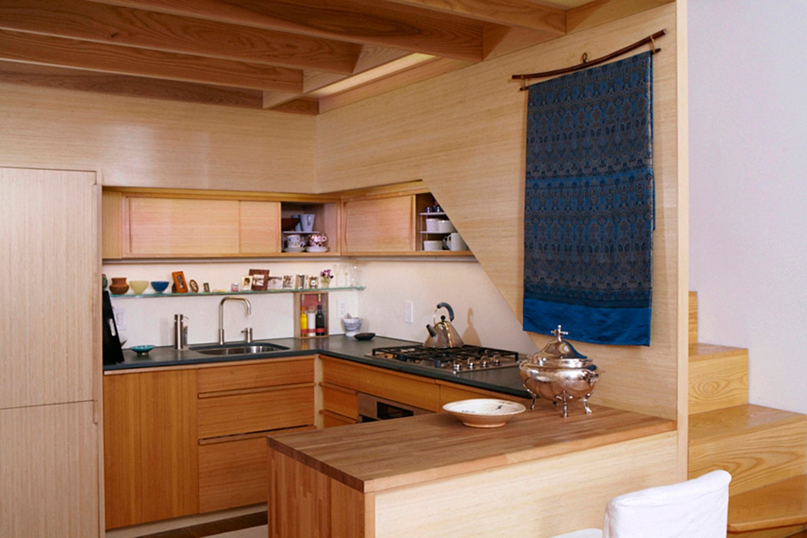 Kitchen, Wood Counter, Wood Cabinet, Refrigerator, Range, Wall Oven, and Undermount Sink In this truly tiny apartment, a 240-square-foot shoebox of an apartment in NYC with a sleeping loft over the kitchen, architect Tim Seggerman went straight to his toolbox to craft a Nakashima-inspired interior. Photo by David Engelhardt.  Photo 6 of 8 in Space-Saving Wood-Paneled Apartment in Manhattan
