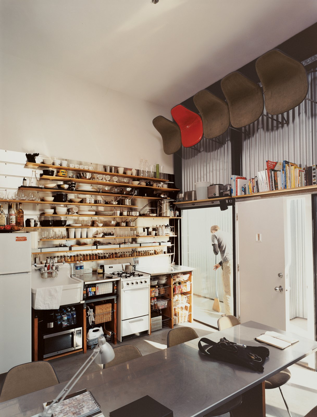 "Kitchen and Wood Cabinet The computer-designed kitchen area has the feel of a ship's galley, with everything neatly stowed, yet visible and instantly at hand: It's much the definition of ""ship-shape."" For dinner parties, well-worn Eames shell chairs are pulled down by David, with the help of a footstool. ""I have nearly an eight-foot reach,"" says the 6'3'' David. (""It gets a little tough if I have to spend a weekend or so alone,"" says Im.)  One-Room Wonders from Modern Mixed Use in San Diego"