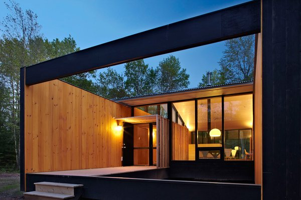 A corrugated metal roofing, pine walls stained a warm blonde hue, and an abundance of glass make this modern prefab feel much roomier than its 1,600-square-feet size.