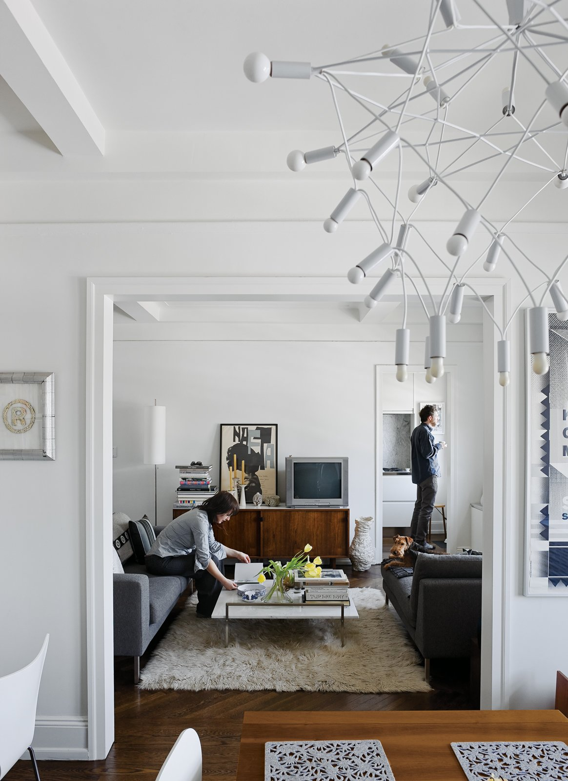 Living Room, Sofa, and Coffee Tables Up on the ninth floor, their sober Neo sofa and chaise from DWR and classic Florence Knoll credenza are contrasted by more exotic accessories like Patrick Townsend's Orbit chandelier and an offbeat white vase from Creative Growth, an Oakland, California, workshop for disabled artists.  Photo 2 of 13 in Creative Renovation in Brooklyn