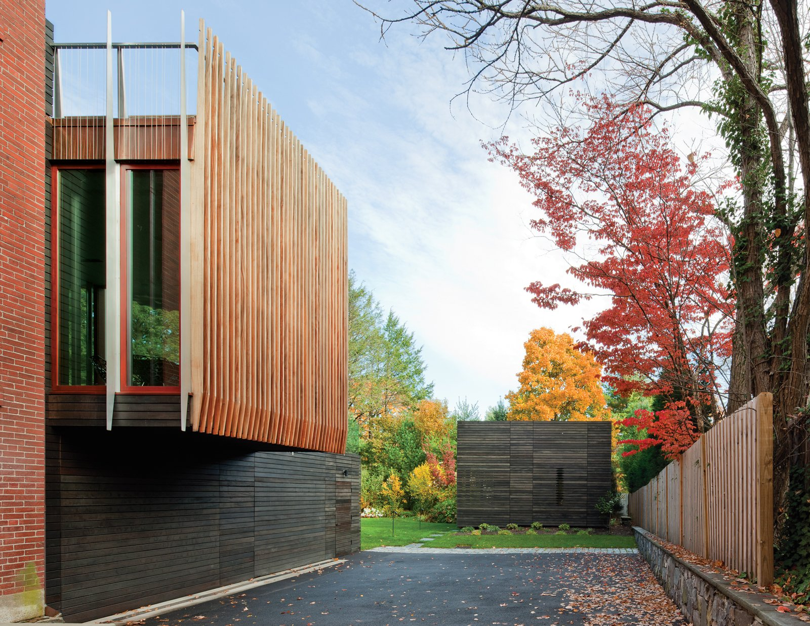 """Exterior Architecture firm NADAAA planned a striated addition to a brick neo-Georgian house in Boston with the owners' primary goal in mind: to engage with the outdoors year-round. The walls of the rear kitchen and living space are virtually all glass, allowing sight lines to the existing gardens and new pool house through a series of framed vignettes onto the backyard landscape. The glass box is bookended by uniform """"fins"""" that mark the edge of each picture window, as shown here. Photo by John Horner.  Best Photos from Facade Focus: Wood"""