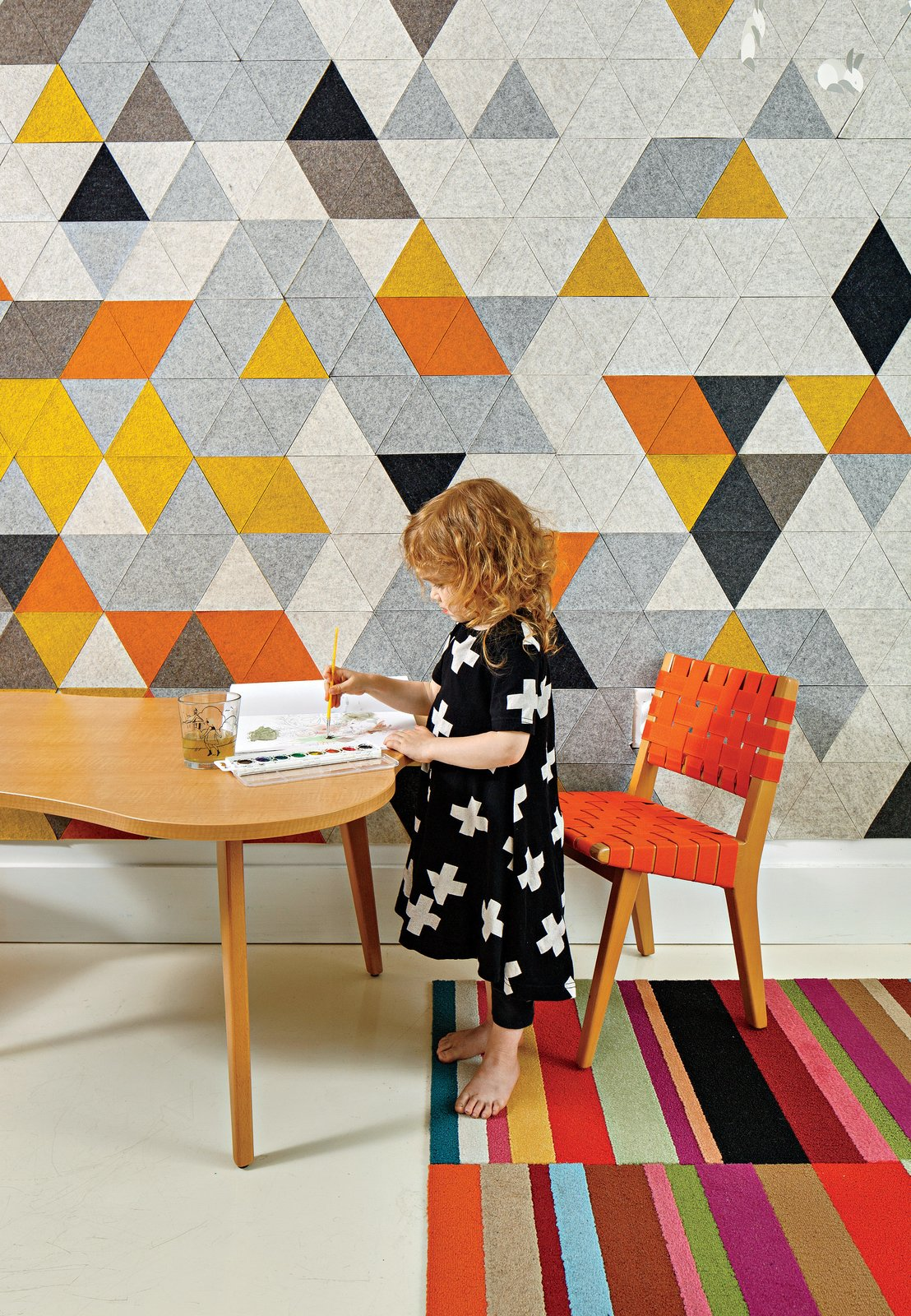 Kids Room, Playroom Room Type, Chair, Desk, and Rug Floor Chris Grimley and Kelly Smith transformed a cramped apartment into a family-friendly home. The room shared by Mae, three, and her little brother Roen, one, features a custom prototype mural by FilzFelt, their mother's textile design company. The carpet is by Flor, and the child-size chair and Amoeba table are both by Jens Risom for Knoll.  Photo 1 of 8 in Boston Renovation Accents Minimalist White with Rich Felt Murals