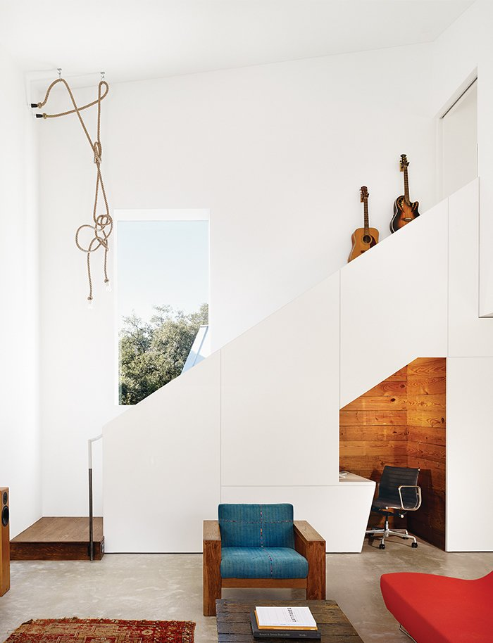 Staircase Sam Shah and Anne Suttles asked architect Kevin Alter to renovate their 1920s bungalow in Austin, Texas, and add an addition, which contains a living area downstairs and an office upstairs. They tucked an office nook under the stairs; the Eames chair is a hand-me-down from Shah's father.  Storage from 1920s Bungalow Plus Modern Addition Equals Perfect Austin Home
