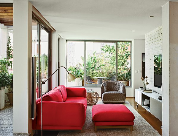 The living room is furnished with a cherry-red Rest sofa and ottoman by Muuto, a Nest footstool by Foersom & Hjort-Lorenzen for Cane-Line, and a Redondo armchair by Patricia Urquiola for Moroso. A Kast modular storage unit by Maarten Van Severen for Vitra sits under the television.