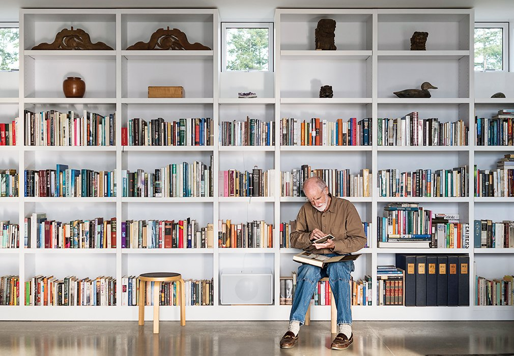 Living Room, Bookcase, Concrete Floor, and Stools In the living area, Brothers sits on an Artek stool while perusing a selection from his library.  Photo 11 of 18 in Idyllic Home Designed for an Artist