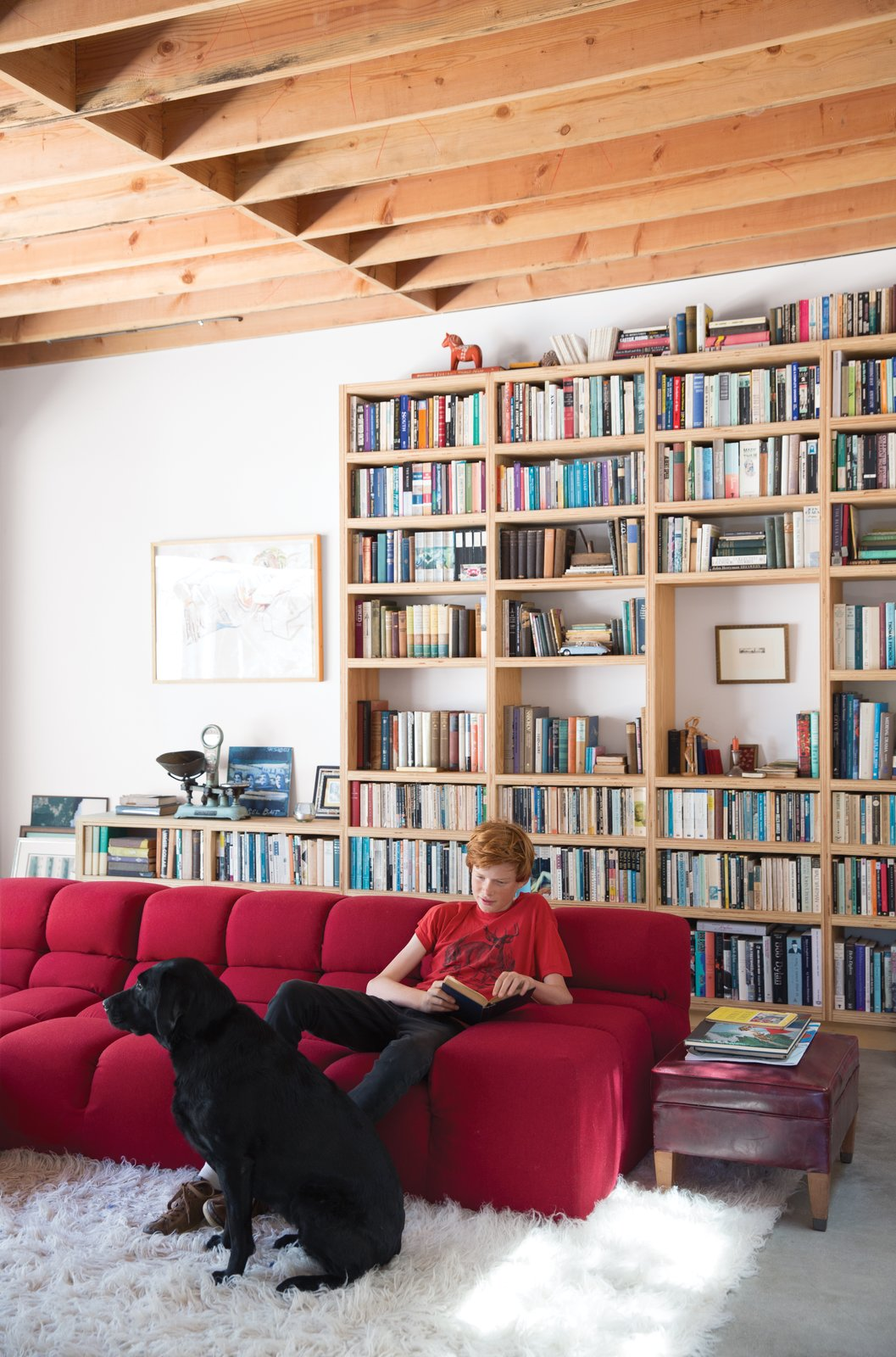 Living Room, Sofa, Bookcase, and Concrete Floor Wes Mahony lounges on a Tufty-Time sofa by Patricia Urquiola for B&B Italia in the family room that architect Emily Jagoda created for his family in their tree-damaged garage in Santa Monica.  Instances of Patricia Urquiola-Designed Pieces in Modern Homes by Zachary Edelson from The Garage That's as Fun as the Living Room