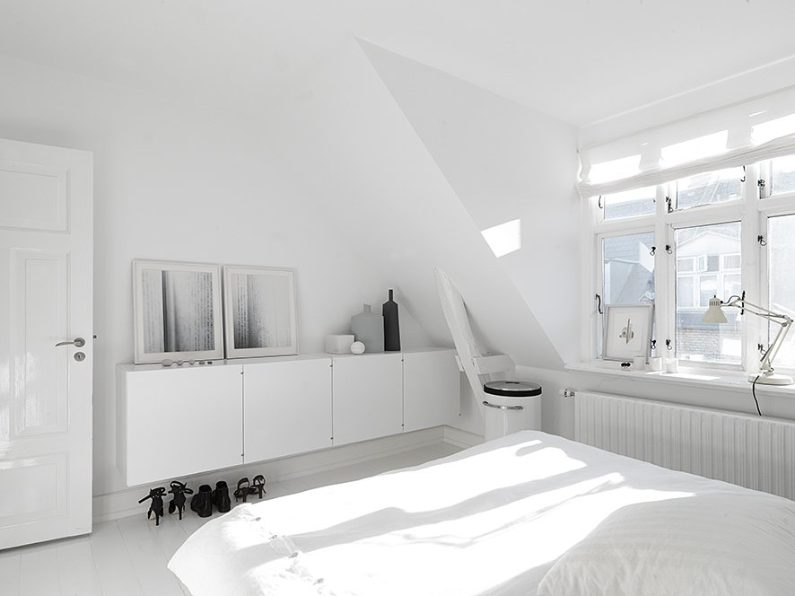 Bedroom, Bed, Dresser, and Painted Wood Floor On the upper floors, bright white walls and plenty of natural light make the bedrooms and living rooms feel large and spacious. In the master bedroom, built-in cabinetry hides clutter. The art photography against the wall is by Anders Hviid, the bed is Hästens, the laundry basket is Vipp, and the lamp is Fontana Arte.  Modern Danish Homes We Love from Black, White, and Gray All Over: Monochromatic Copenhagen Townhouse