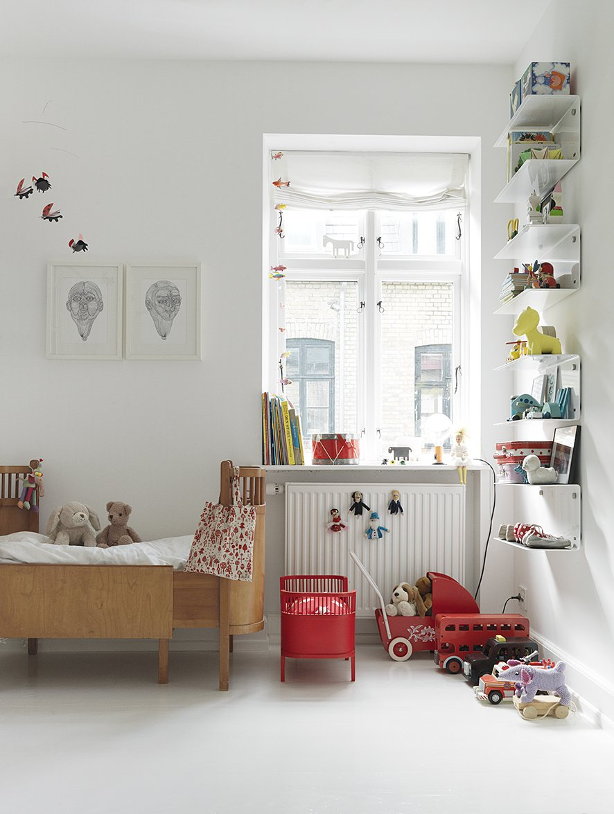 Kids, Bed, Shelves, Bedroom, Painted Wood, Toddler, and Neutral Even the children's rooms, though peppered with colorful details, retain the stark white walls and minimal feel of the rest of the Egelunds' home. The wooden bed is by Juno, the doll bed are by Flos Lampadina, and the shelves are Vipp.  Kids Painted Wood Photos from Black, White, and Gray All Over: Monochromatic Copenhagen Townhouse