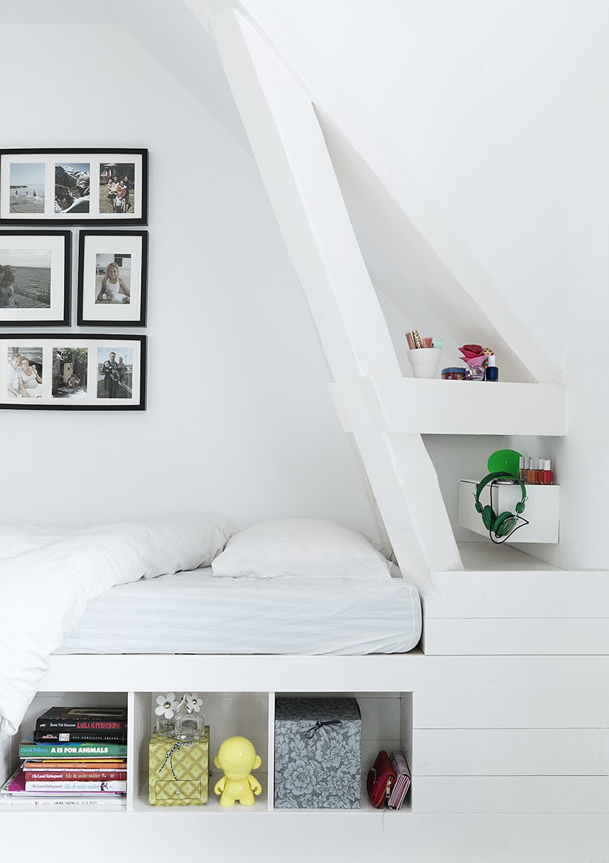 Bedroom, Bed, and Storage Custom details like this corner bed with built-in shelving keep the younger generation's spaces playful, but still sophisticated. With four children, utilizing space wisely became a top priority, and the family relies on custom shelving and built-ins to keep clutter at bay. The bed is custom with IKEA frames.  Bedrooms by Dwell from Black, White, and Gray All Over: Monochromatic Copenhagen Townhouse