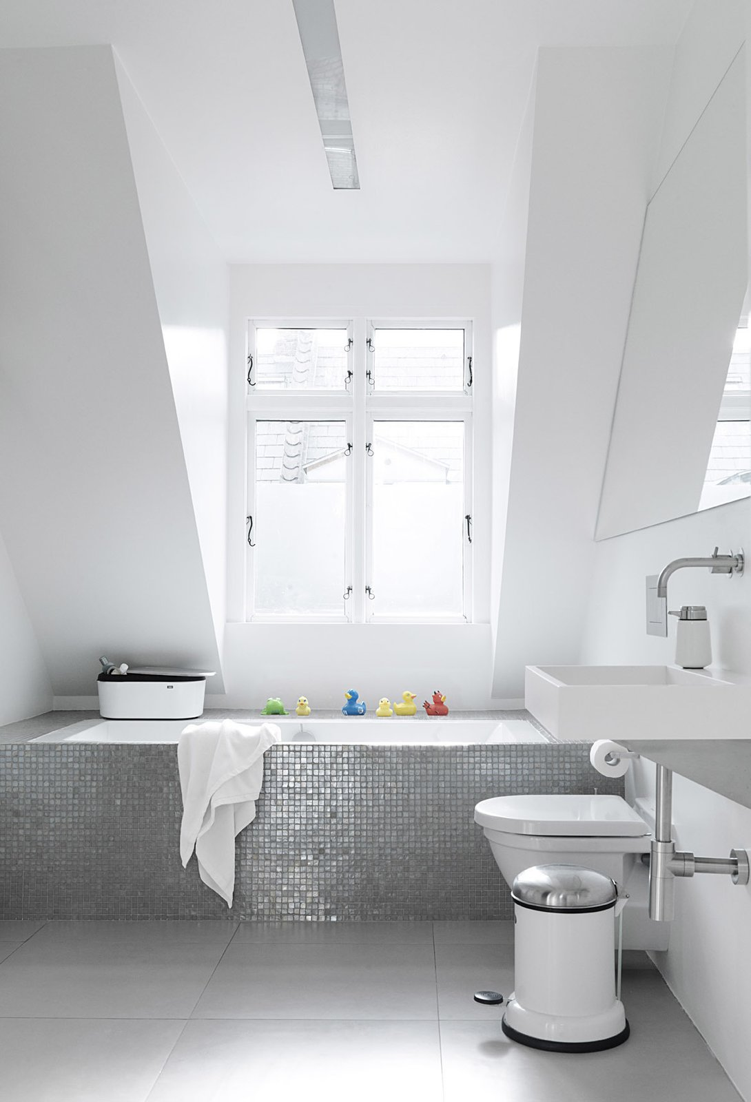 Bath Room, Drop In Tub, and Wall Mount Sink Sofie and Frank built a box around an ordinary glass fiber shell bathtub, then covered it in a mosaic of shower tiles. Natural light from a large dormer window gives the tiles an almost iridescent glow. The toilet is Duravit.  Photo 10 of 12 in Black, White, and Gray All Over: Monochromatic Copenhagen Townhouse