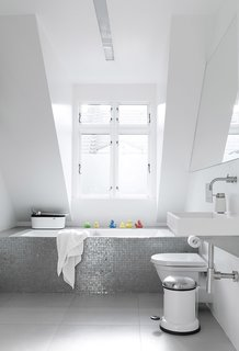Sofie and Frank built a box around an ordinary glass fiber shell bathtub, then covered it in a mosaic of shower tiles. Natural light from a large dormer window gives the tiles an almost iridescent glow. The toilet is Duravit.
