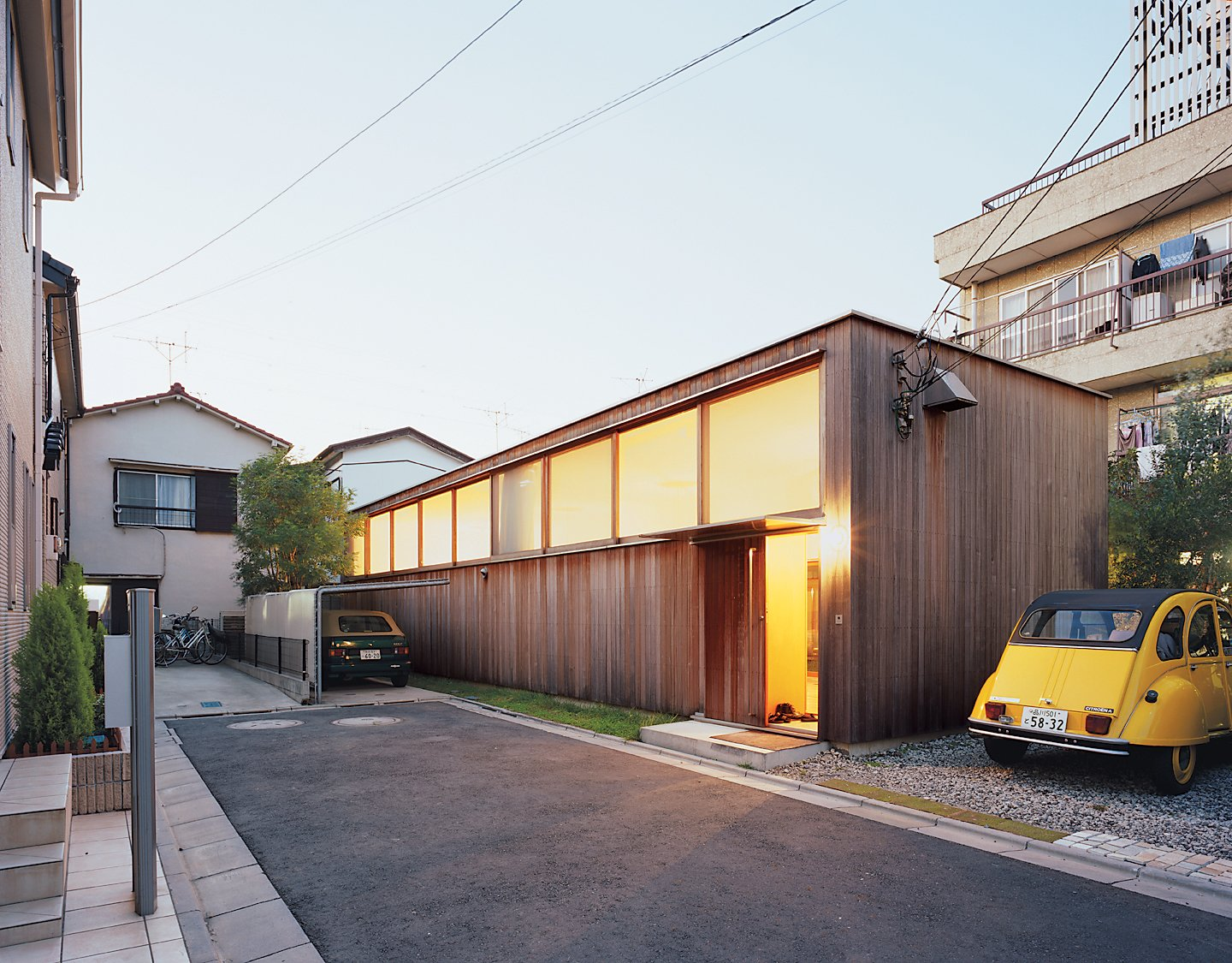 Exterior, Wood Siding Material, House Building Type, and Flat RoofLine Large clerestory windows face the street at the Higashibatas' house in Tokyo, optimizing both privacy and natural light within.  Photo 3 of 12 in Family Style