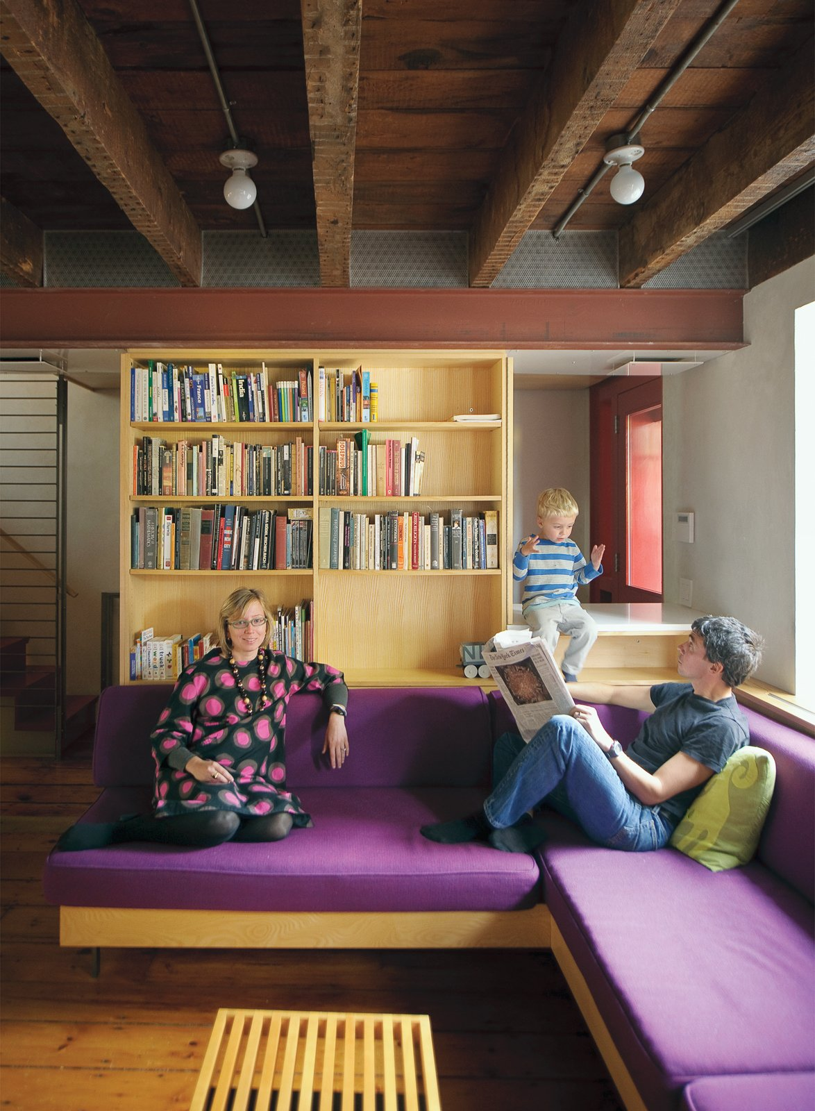 Living Room, Bookcase, Medium Hardwood Floor, and Sectional The exposed ceiling beams and inserted steel framing system are visible in the lower level, where Lange and Dixon relax with their son Paul.  Best Photos from Family Home Renovation in Brooklyn