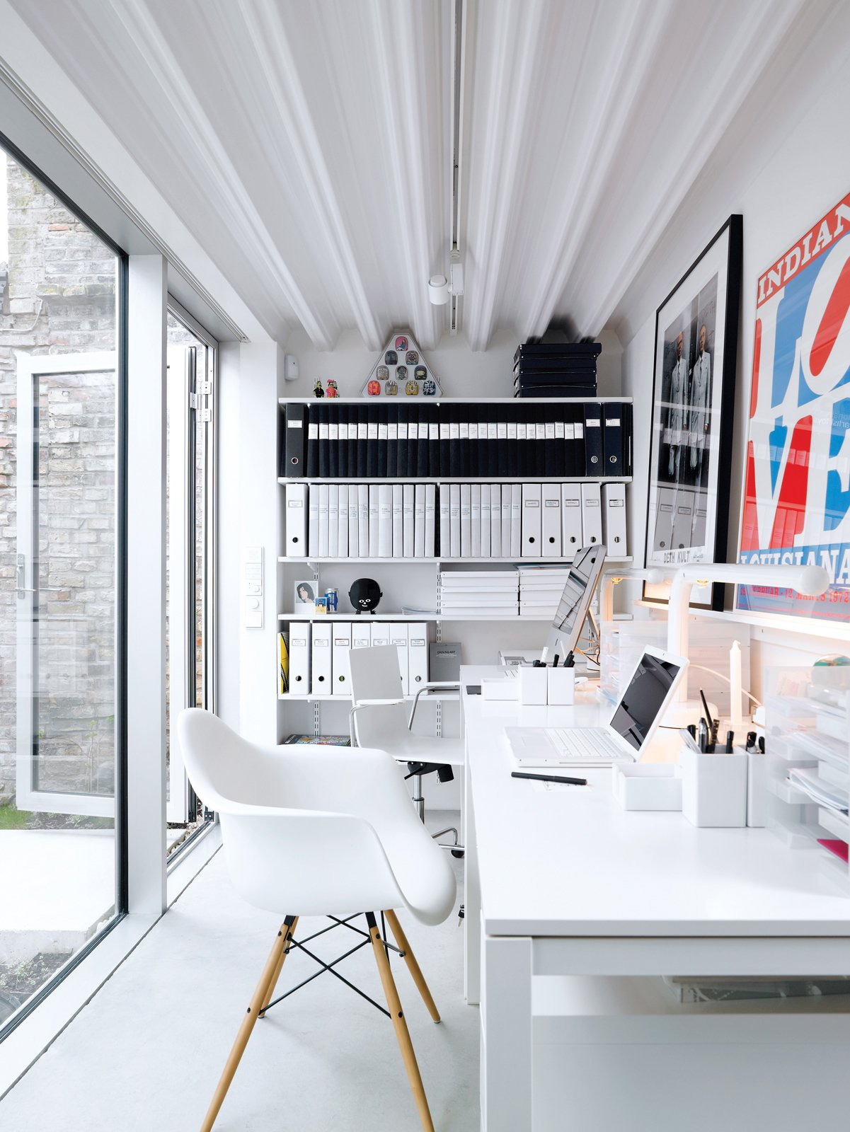 Office, Desk, and Chair The office, which is a single-level separate unit, boasts Ikea desks and a signed work by Gilbert and George (friends of the couple).  Photo 8 of 14 in Contemporary Nordic Town House