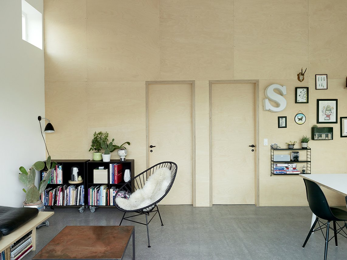 """The house uses only three interlocking materials: a self-heated concrete floor that eliminates the need for space-consuming radiators; double-glazed windows that let the outdoors in while keeping out the cold; and eight wooden panels manufactured in a Denmark factory during the winter months. """"The interior walls are birch plywood to add warmth and texture to the rooms,"""" Larsen says.  Danish Prefab Feels Much Larger Than Its 861 Square Feet by Laura C. Mallonee"""