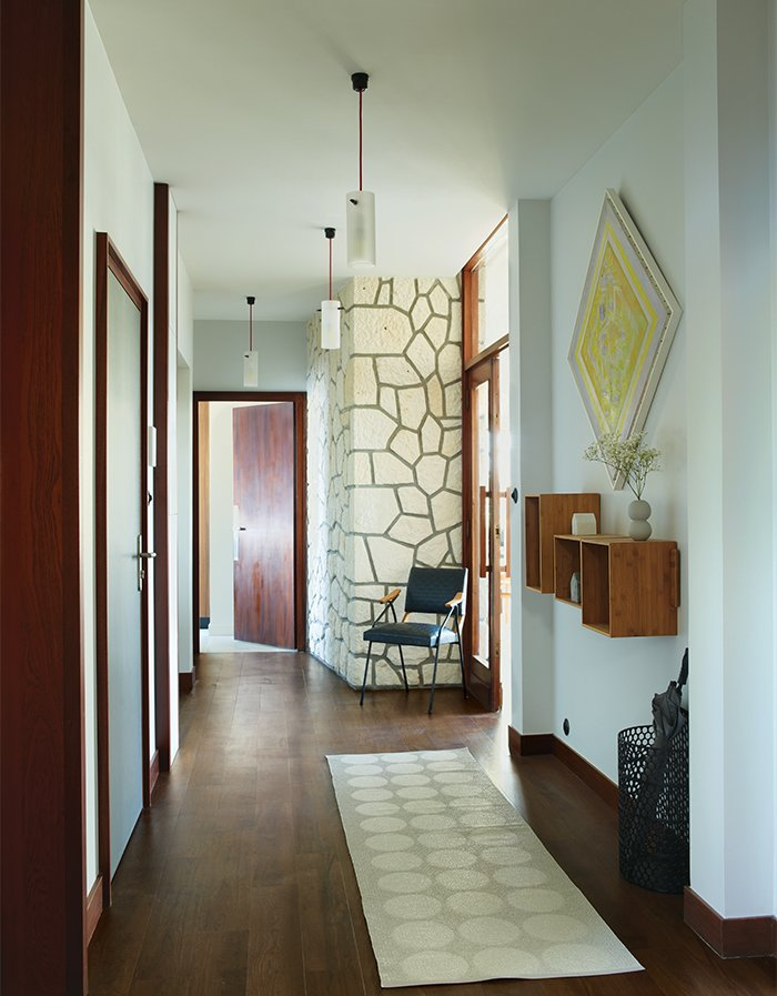 Hallway, Rug Floor, and Dark Hardwood Floor Shelves from Danish company We Do Wood, pendants by Uno & Osten Kristensson, a rug by Pappelina, and a vintage chair adorn the entry hallway. The wood doors and frames are original.  Photo 13 of 17 in Modern Home Furnished With Flea Market Finds