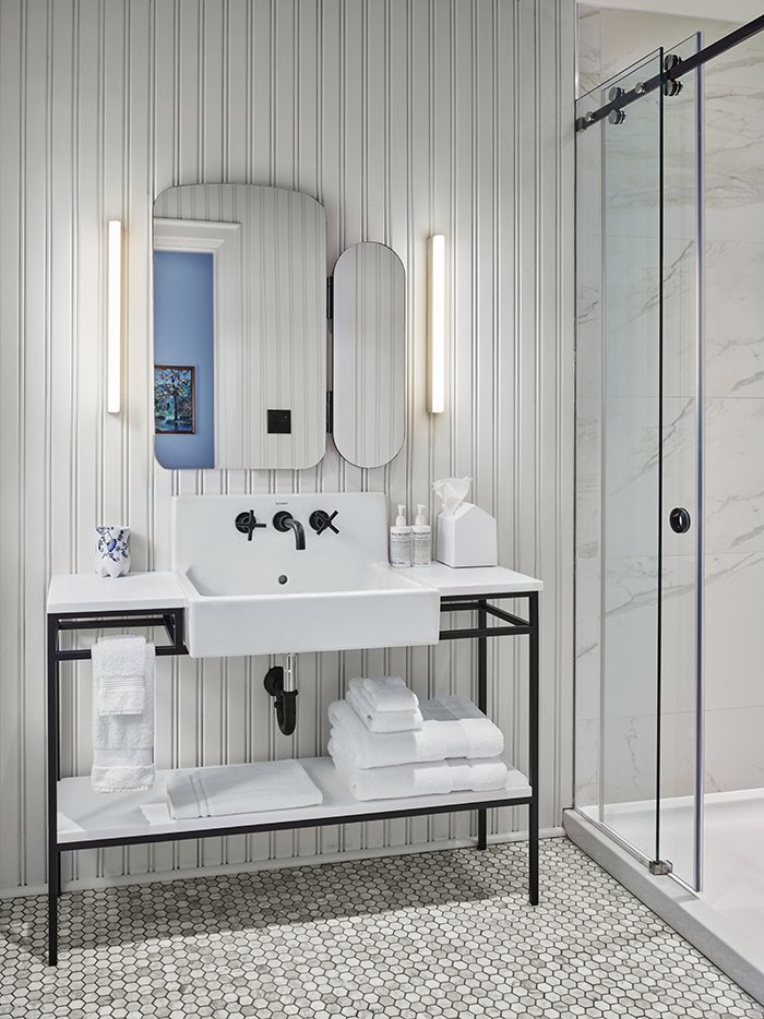 Bath Room, Pedestal Sink, Wall Lighting, Enclosed Shower, and Porcelain Tile Floor One of many popular designs for modern bathroom vanities is open rather than closed shelving. This design element is on display here, where this freestanding vanity offers ample storage.   Photo 10 of 25 in 25 Best Modern Bathroom Vanities For Your Home from Modern Boutique Hotel in a 19th-Century Foundry