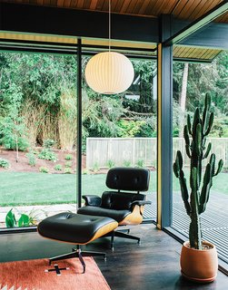 In true mid-century fashion, a George Nelson Bubble Lamp is paired with an Eames Lounge by Charles and Ray Eames in a corner of the living room. The glass walls and mitered corner are original features of architect Saul Zaik's 1956 design.