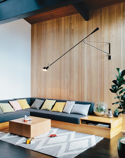 The sofa in the family room was designed by Helgerson with Magnifique fabric by Kravet. The 265 Wall Lamp is by Paolo Rizzatto for Flos, and the pine coffee table is from The Good Mod, a local shop in Portland.