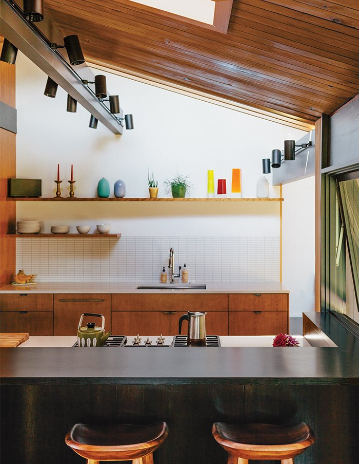 Kitchen and Wood Cabinet For the kitchen, master bath, and kids' bathroom, the designers chose three different hues of Savoy stacked mosaic tile from Portland-based manufacturer Ann Sacks. Tractor barstools by BassamFellows pull up to a PentalQuartz countertop. The gas cooktop, oven, and dishwasher are by Miele.  Photo 6 of 19 in Midcentury Renovation in Portland Capitalizes on Nature with Seven Doors to the Outside