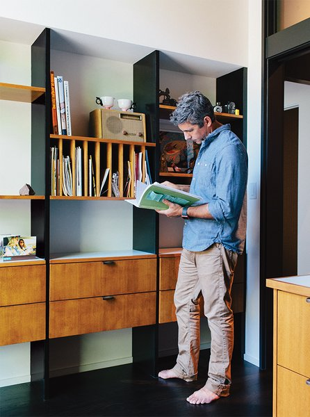 Resident Ty Milford peruses a book by the George Nelson–inspired built-ins fabricated by Big Branch Woodworking