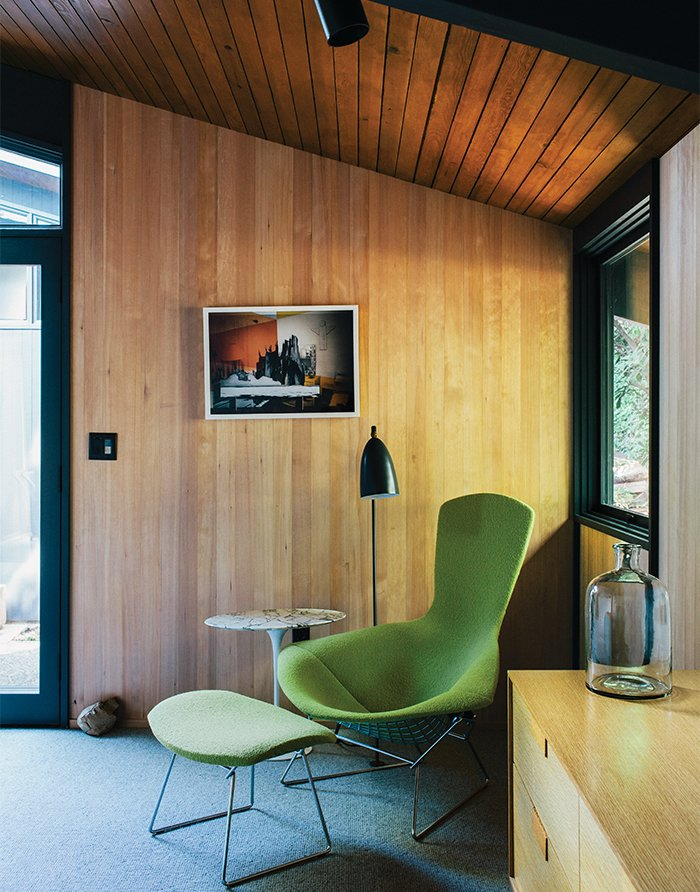 The wool carpet is from Iberia. A Bird Chair by Harry Bertoia for Knoll and a Grasshopper Lamp by Greta Grossman round out the room.  Photo 12 of 19 in Midcentury Renovation in Portland Capitalizes on Nature with Seven Doors to the Outside