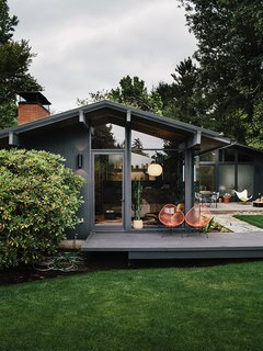 The exterior sconces are original to Zaik's 1956 design. JHID rebuilt the rear deck off the living room, which connects to an aggregate patio; the two architectural elements are connected by pathways in variegated bluestone designed by Lilyvilla Gardens.