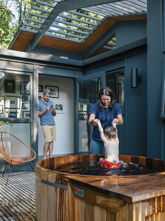 Kelly Milford helps son Adam out of the hot tub nestled on a wood deck in back of the house. The exterior paint is Wrought Iron by Benjamin Moore.