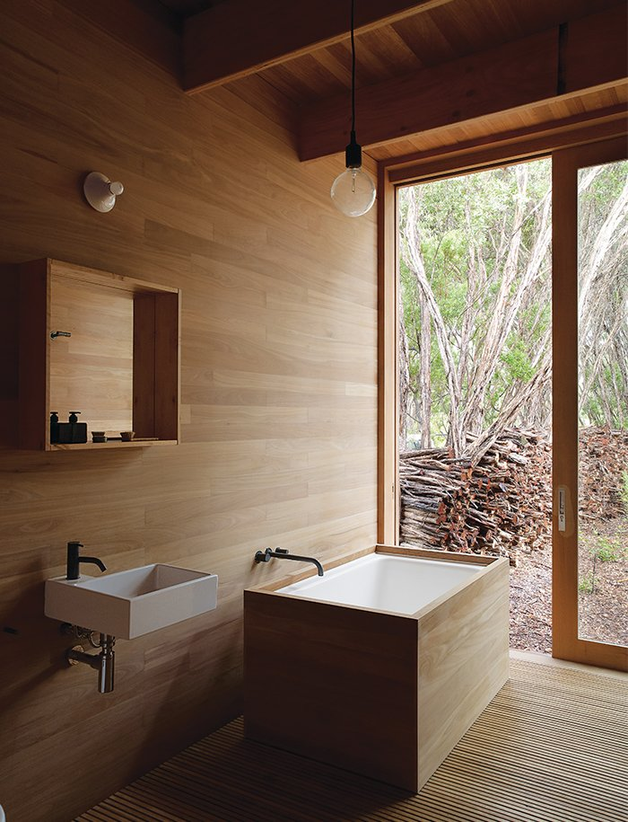 Houle designed the ofuro tub in the master bath to mesh with the home's tallowwood wall paneling. The Ikea sink is outfitted with Vola faucets. Tagged: Bath Room, Freestanding Tub, Medium Hardwood Floor, Wall Lighting, Pendant Lighting, Wall Mount Sink, Undermount Tub, and Soaking Tub.  Nippon inspired from Local Wood Clads Every Surface of This Idyllic Australian Getaway