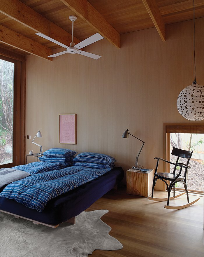 Bedroom, Bed, Lamps, Table Lighting, Pendant Lighting, Light Hardwood Floor, Night Stands, and Rug Floor In the master bedroom, the rocking chair is by Thonet and the bespoke rug is by Armadillo & Co.  Bedrooms by Dwell from Local Wood Clads Every Surface of This Idyllic Australian Getaway