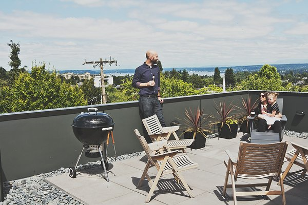 Outdoor, Hardscapes, Rooftop, and Raised Planters Rex folding rocker chairs from Design Within Reach are paired with black galvanized-steel planters from Ikea on the building's roof deck.  City Homes with Astounding Views by Luke Hopping from Green and Affordable Structure Fits Three Families in One 28-Foot-Wide Lot