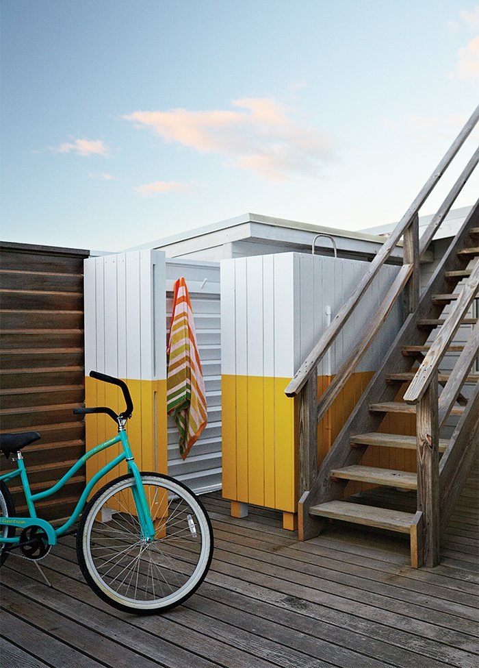 The wood screen concealing the outdoor shower was painted yellow and white, matching the color scheme in the guest bathroom.  Photo 6 of 11 in How to Build an Outdoor Shower from Smart Interior Update Shows When a Gut Renovation Isn't Necessary